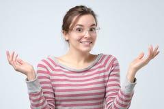 Femme gesticulant des mains et exprimant la confusion, n'ayant pas tout indice image stock