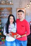 Femme gifting d'homme heureux présente dans la chambre décorée, célébrant Noël photographie stock
