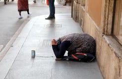femme gitane demandant l'aumône se mettant à genoux au sol avec sa main photo libre de droits