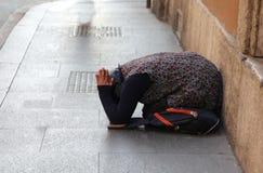 Femme gitane pluse âgé demandant l'aumône se mettant à genoux au sol avec photos stock