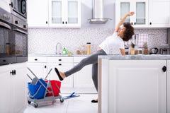 Femme glissant tout en essuyant le plancher dans la cuisine photographie stock libre de droits