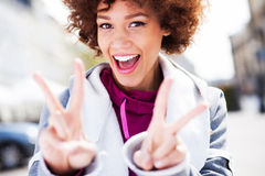 Femme géniale donnant un signe de paix Image stock