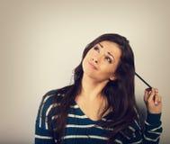 Femme grimaçante de brune de confusion imaginant et regardant avec image stock
