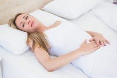 Femme grimaçante souffrant avec douleur abdominale Images libres de droits