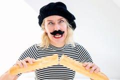 Femme habillée en tant qu'homme français avec la barbe et le béret et la baguette image libre de droits