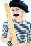 Femme habillée en tant qu'homme français avec la moustache et le béret tenant le bagu image stock