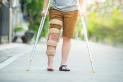 Femme handicapée avec la position de soutien de béquilles ou de bâton ou de genou de marche dans l'arrière, demi corps photographie stock libre de droits