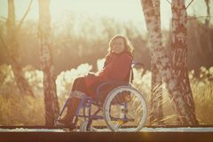 Femme handicapée de sourire sur le fauteuil roulant en hiver Photographie stock libre de droits