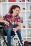 Femme handicapée employant l'aspirateur à la maison image libre de droits