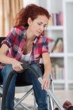 Femme handicapée employant l'aspirateur à la maison photo stock