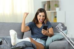 Femme handicapée enthousiaste recevant des actualités en ligne photos libres de droits