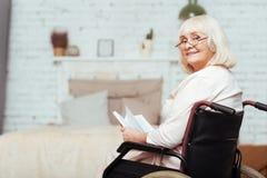 Femme handicapée pluse âgé positive se reposant à la maison Photographie stock libre de droits