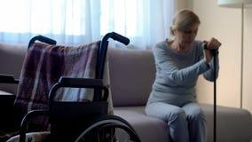 Femme handicapée s'asseyant sur le sofa et pleurant, fauteuil roulant vide dans la chambre, solitude image stock