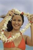 Femme hawaïen donnant des leu d'une fleur Photo stock