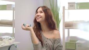 Femme heureuse à l'aide de l'inhalateur pour le souffle frais dans la salle de bains Soin dentaire et de dents banque de vidéos