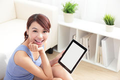 Femme heureuse à l'aide du PC de comprimé sur le sofa Photo libre de droits