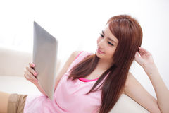 Femme heureuse à l'aide du PC de comprimé sur le sofa Photos stock