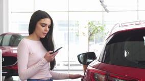Femme heureuse à l'aide du téléphone intelligent au concessionnaire automobile banque de vidéos