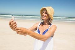 Femme heureuse à l'aide du téléphone intelligent tout en se tenant à la plage Images stock