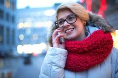 Femme heureuse à l'aide du téléphone portable dehors pendant l'hiver images libres de droits