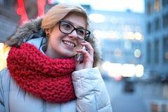 Femme heureuse à l'aide du téléphone portable dehors pendant l'hiver images stock