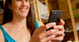 Femme heureuse à l'aide du téléphone portable tout en faisant des emplettes dans le supermarché 4k banque de vidéos