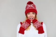Femme heureuse étonnée regardant en longueur dans l'excitation Fille de Noël utilisant le chapeau tricoté et les mitaines chauds, image stock
