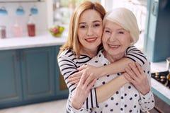 Femme heureuse étreignant sa mère plus âgée dans la cuisine Photographie stock libre de droits