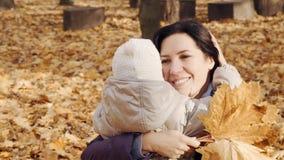 Femme heureuse étreignant sa petite fille en parc d'automne clips vidéos