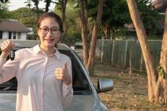 Femme heureuse achetant la nouvelle voiture Conducteur femelle montrant la clé de voiture photographie stock