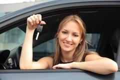 Femme heureuse affichant la clé d'un véhicule neuf Photo stock