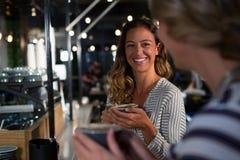 Femme heureuse agissant l'un sur l'autre tout en ayant le café Photographie stock