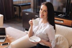 Femme heureuse agréable ayant le café Photos stock