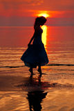 Femme heureuse appréciant dans le coucher du soleil de mer Silhouetté contre les soleils Photos libres de droits