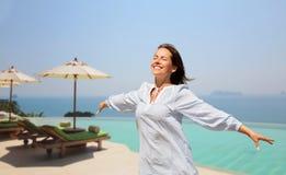 Femme heureuse appréciant le soleil au-dessus de la piscine de bord d'infini image libre de droits