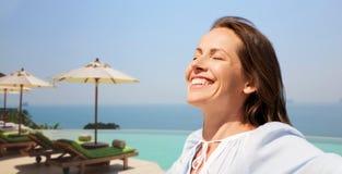 Femme heureuse appréciant le soleil au-dessus de la piscine de bord d'infini image stock