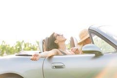 Femme heureuse appréciant le voyage par la route dans le convertible avec l'ami Photo stock