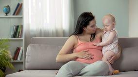 Femme heureuse attendant le deuxième bébé, disant le premier enfant au sujet du frère ou de la soeur photo stock