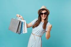 Femme heureuse attirante à la mode de portrait dans la robe d'été, chapeau de paille, lunettes de soleil tenant des sacs de paque photographie stock libre de droits