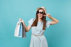 Femme heureuse attirante à la mode de portrait dans la robe d'été, chapeau de paille, lunettes de soleil tenant des sacs de paque photos stock