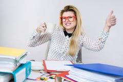 Femme heureuse au bureau buvant du café chaud photographie stock libre de droits