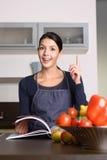 Femme heureuse au comptoir de cuisine avec le livre de recette Photographie stock libre de droits