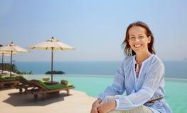 Femme heureuse au-dessus de fond de piscine de bord d'infini image libre de droits