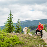 Femme heureuse augmentant la marche avec le chien en montagnes, Pologne Images stock