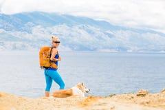 Femme heureuse augmentant la marche avec le chien sur la traînée de bord de la mer Image libre de droits