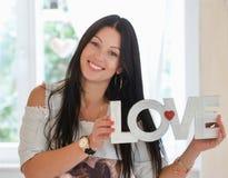 Femme heureuse avec amour de mot se tenant à la maison Photo libre de droits