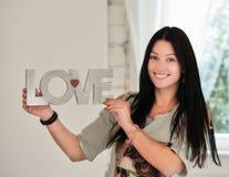 Femme heureuse avec amour de mot se tenant à la maison Photographie stock