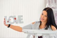 Femme heureuse avec amour de mot se tenant à la maison Photos libres de droits