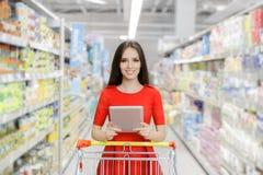 Femme heureuse avec des achats de Tablette au supermarché image libre de droits