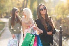 Femme heureuse avec des achats sur un fond des amis Photo libre de droits